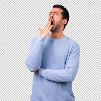 Man with blue sweater yawning and covering wide open mouth with hand. sleepy expression