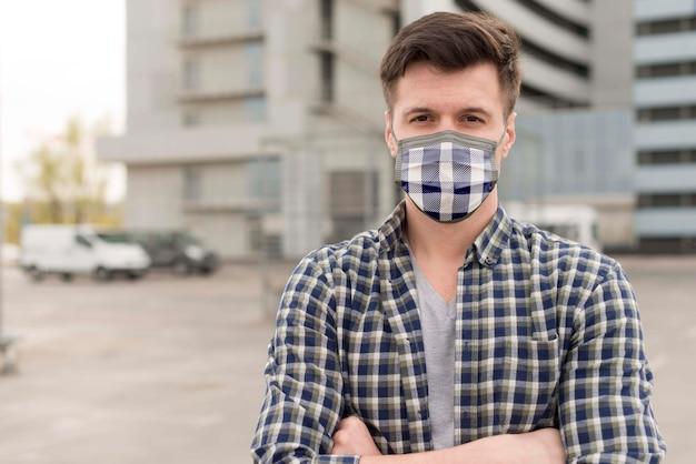 顔に布マスクを持つ男