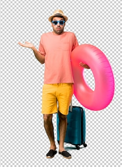 Man with hat and sunglasses on his summer vacation having doubts and with confuse face expression while raising hands and shoulders uncertain concept