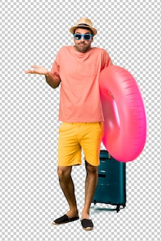 Man with hat and sunglasses on his summer vacation making unimportant and doubts gesture while lifting the shoulders and the palms of the hands