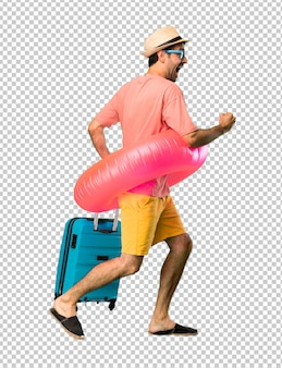 Man with hat and sunglasses on his summer vacation running fast