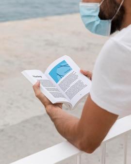Человек с маской на улице, читая книгу