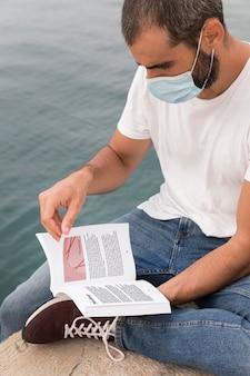 Uomo con la maschera sul libro di lettura di strada