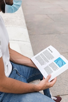 Man with mask on street reading book