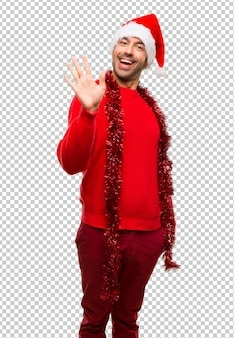 Man with red clothes celebrating the christmas holidays saluting with hand with happy expression