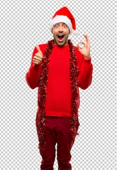 Man with red clothes celebrating the christmas holidays showing ok sign
