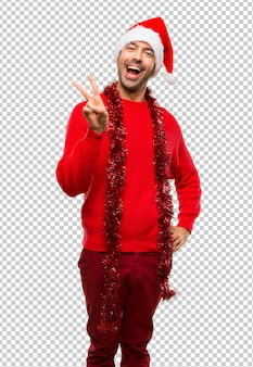 Man with red clothes celebrating the christmas holidays smiling and showing victory sign