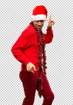 Человек с красной одеждой, празднующий рождественские праздники, любит танцевать, слушая м