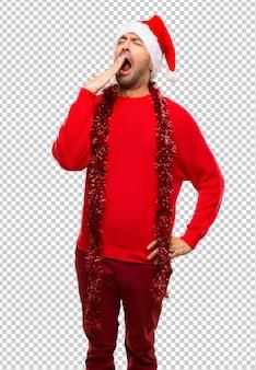 Человек с красной одеждой празднует рождественские праздники, зевая и покрывая широко открытые моу