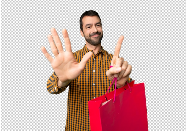 指で6を数える買い物袋を持つ男
