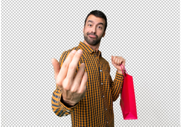 Man with shopping bags inviting to come with hand. happy that you came