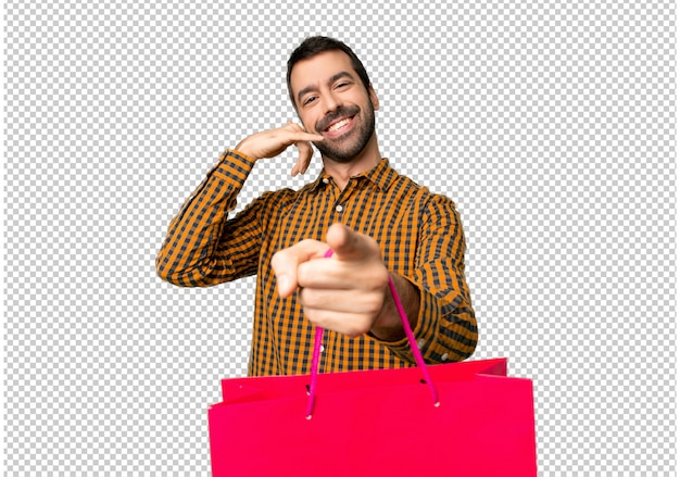 Man with shopping bags making phone gesture and pointing front