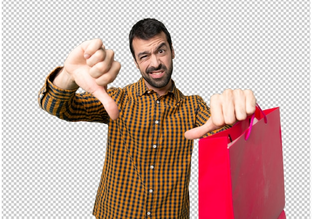 Man with shopping bags showing thumb down with both hands