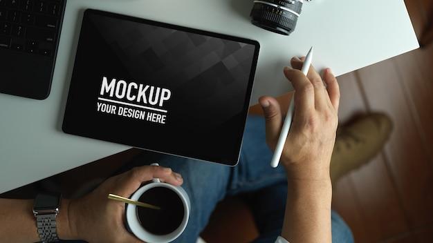 작업 공간에서 커피 컵을 마시는 동안 모형 화면 태블릿에서 작업하는 사람