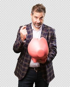 Mature man holding a piggy bank