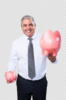 Mature man saving with piggy bank