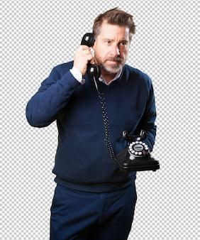電話で話している中年の男性