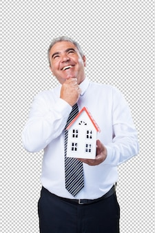 Mature man thinking holding a house
