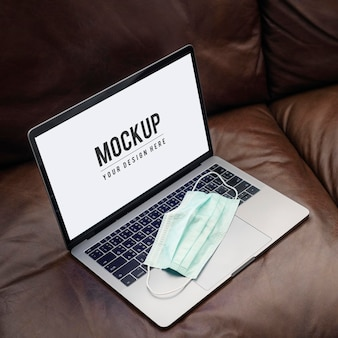 Medical mask on a laptop with a mockup screen