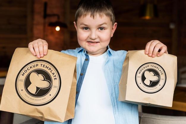 Ragazzo di tiro medio che tiene in mano i sacchetti di cibo
