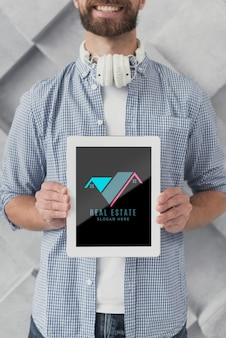 Medium shot of businessman holding a tablet with real estate