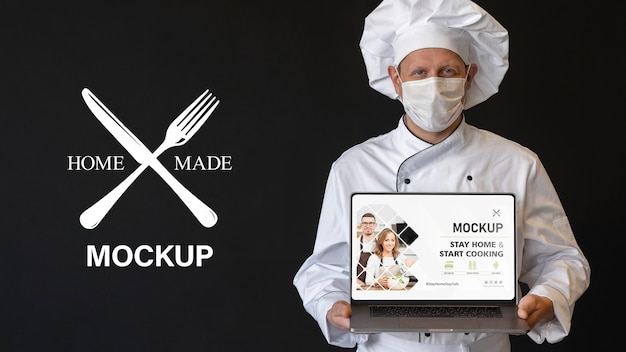 Medium shot chef with mask holding laptop