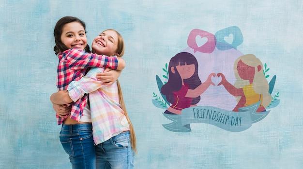 Среднего выстрела маленькие девочки обнимаются с макетом стены