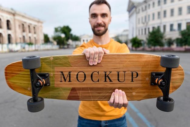 スケートボードを持っているミディアムショットの男