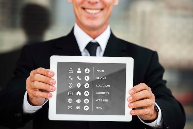 마케팅 목적을 위해 웃는 남자 보여주는 태블릿의 중간 샷