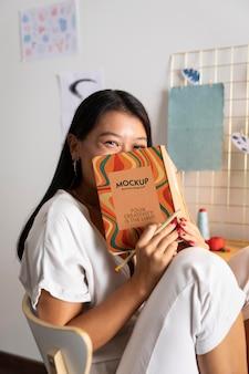 ノートを持っているミディアムショットの女性