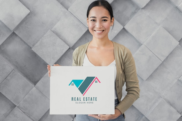 Medium shot of woman holding a poster with real estate