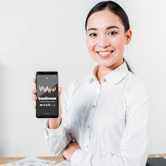Средний выстрел женщина держит смартфон