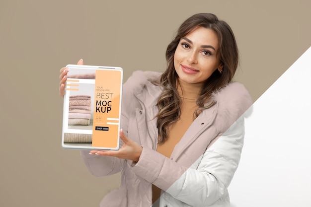 Medium shot woman holding tablet mockup