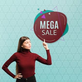 Средняя выстрела женщина, указывая на мега распродажу