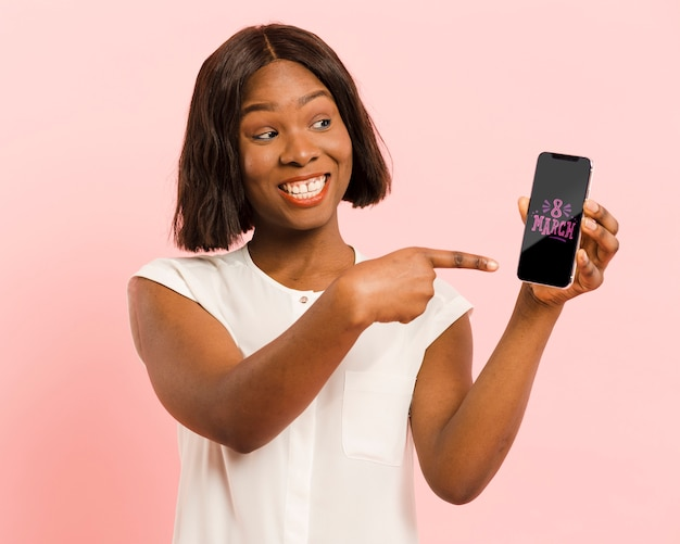 Medium shot woman pointing at her smartphone