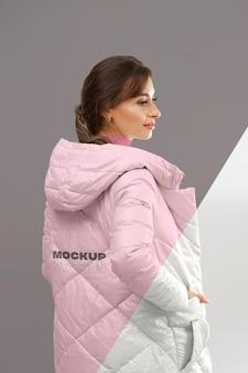 Среднего выстрела женщина представляет зимнюю куртку