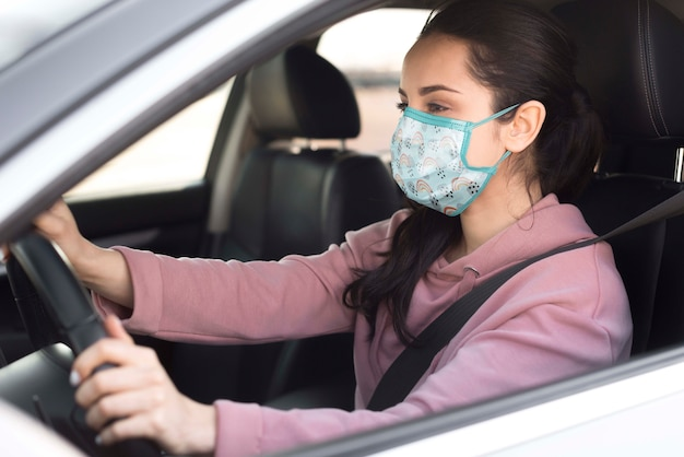 Medium shot woman with mask driving