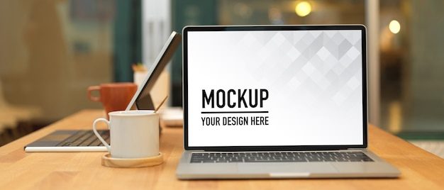 ノートパソコンのモックアップとオフィスルームの事務用品と会議テーブル