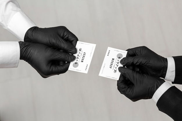 Men with gloves holding business cards mock-up