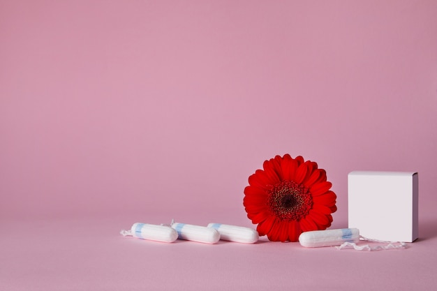 Menstrual tampons and red flower isolated on pink table, top view. copy space