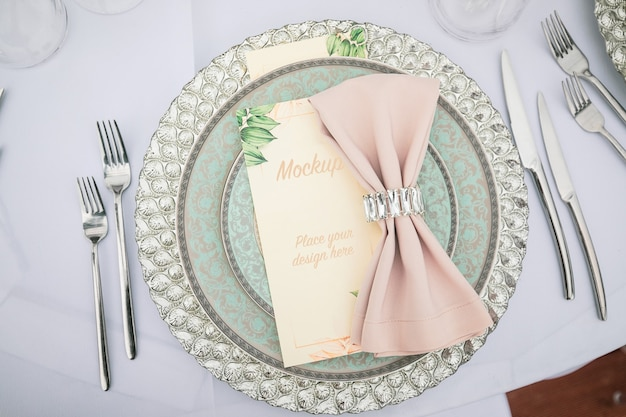 Menu card mockup on laid table decorated with textile napkin