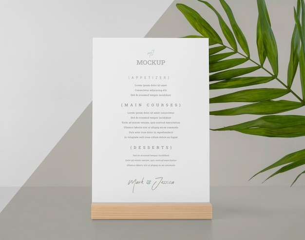 Menu mock-up with wooden stand and leaf