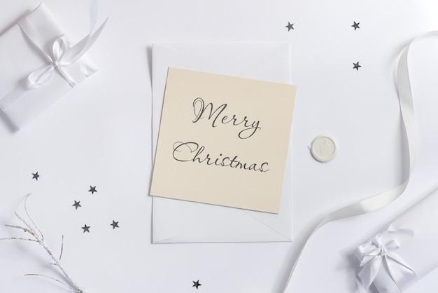 メリークリスマスのグリーティングカードのモックアップとギフトボックス。