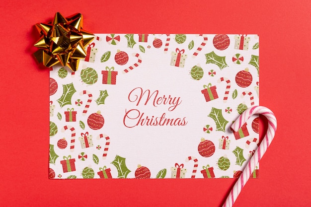 Carta mock-up di buon natale con canna da zucchero e fiocco