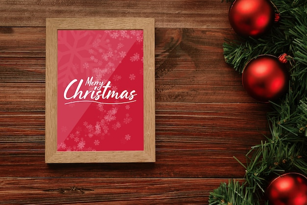Merry christmas photo frame mockup with pine leaves decorations