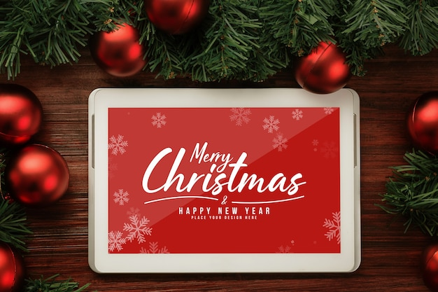 Merry christmas tablet computer mockup with pine leaves decorations