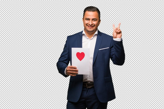 Middle aged latin man celebrating valentines day fun and happy doing a gesture of victory