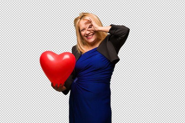Middle aged latin woman celebrating valentines day confident doing ok gesture on eye