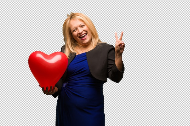 Middle aged latin woman celebrating valentines day doing a gesture of victory