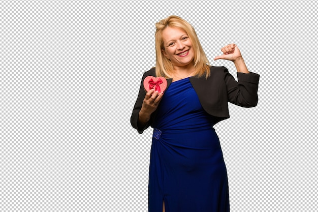Middle aged latin woman celebrating valentines day pointing fingers, example to follow